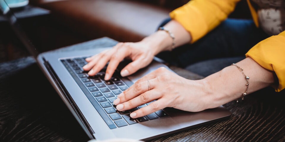 Image of hands on a laptop illustrating taking control of meetings to reclaim your calendar